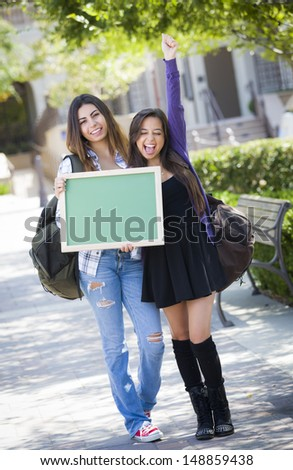 Portrait of Two Attractive Excited Mixed Race Female Students Holding Blank Chalkboard and Carrying Backpacks on School Campus. - stock photo