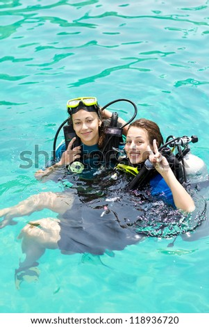 Portrait of two attractive friends going scuba diving - stock photo