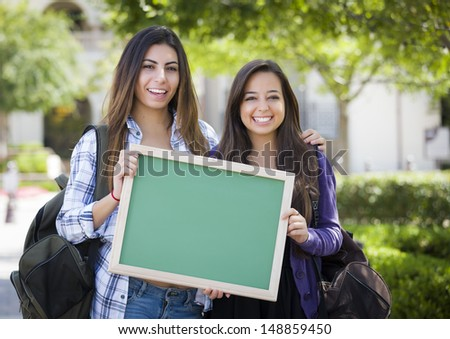 Portrait of Two Attractive Mixed Race Female Students Holding Blank Chalkboard and Carrying Backpacks on School Campus. - stock photo