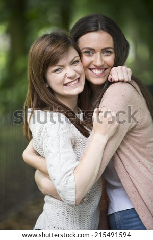 Portrait of two attractive, young caucasian girl friends hugging each other outdoors. - stock photo