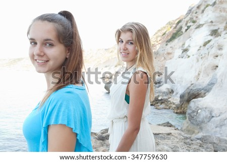 Portrait of two beautiful adolescent friends visiting a rocky beach on holiday, contemplating the sea and turning looking and smiling at the camera, nature outdoors vacation. Teenager lifestyle. - stock photo