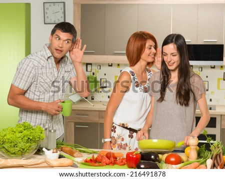 portrait of two beautiful caucasian women standing in kitchen cooking, laughing and whispering something, with one man behing them eavesdropping - stock photo