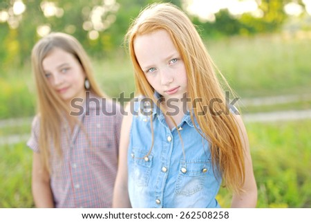 Portrait of two beautiful girlfriends on the nature - stock photo