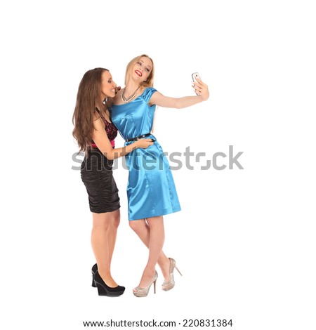 portrait of two beautiful girls making selfies at studio - stock photo