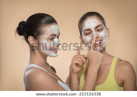 Portrait of two beautiful girls with cream on their  faces looking on each other  and touching their noses and laughing  isolated on beige background - stock photo