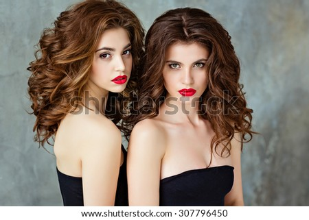 Portrait of two beautiful, glamorous, sensual brunette with gorgeous curly hair and bright makeup with red lipstick, close-up, in the Studio on a gray background, beauty - stock photo