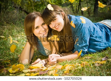 Portrait of Two beautiful happy smiling girls lying in autumn flying leaves outdoors on the forest background
