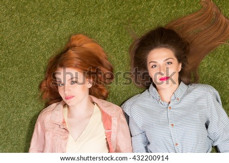 Portrait of two beautiful ladies with red lips lying on green grass and looking at camera. Happy women with long brown hair. - stock photo