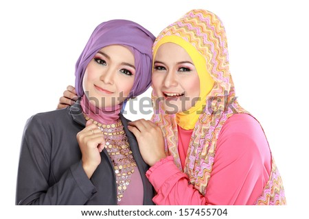 Portrait of two beautiful muslim woman having fun together isolated over white background - stock photo