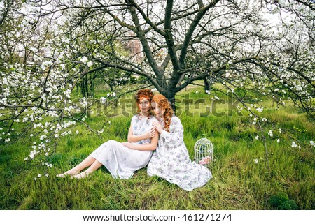 Portrait of two beautiful redhead girls in the spring garden