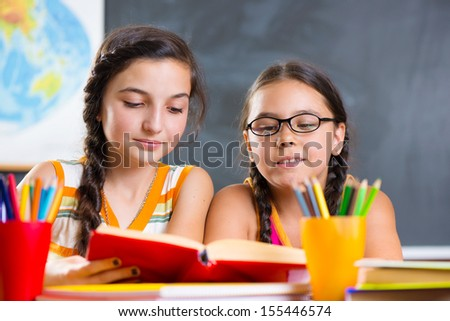 Portrait of two beautiful schoolgirl studying in classroom - stock photo