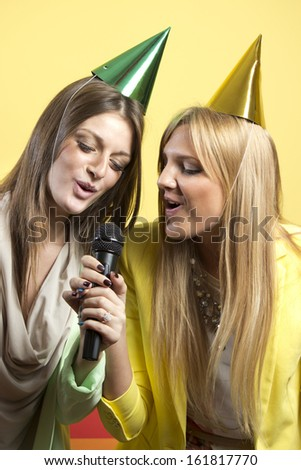 Portrait of two beautiful singing girls - stock photo