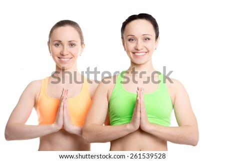 Portrait of two beautiful sporty girlfriends practicing yoga together, hands in Namaste gesture - stock photo