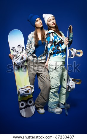 portrait of two beautiful sporty girls with snowboards on blue