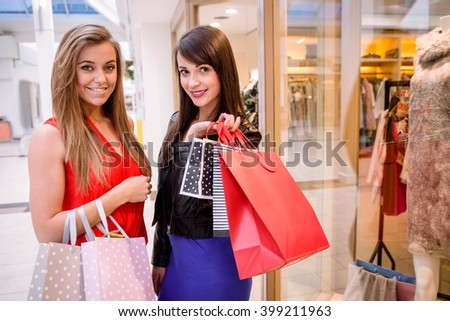 Portrait of two beautiful women holding shopping bags while shopping in mall