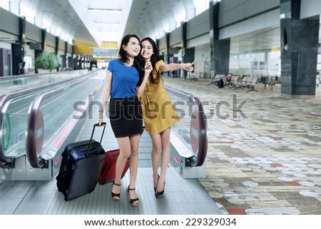 Portrait of two beautiful women looking and pointing something in the airport hall - stock photo