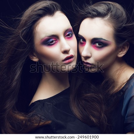 Portrait of two beautiful young girls twins in the studio with bright makeup on a black background
