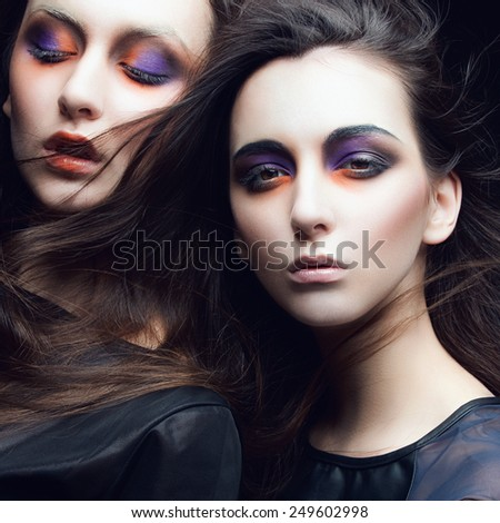 Portrait of two beautiful young girls twins in the studio with bright makeup on a black background, closeup - stock photo