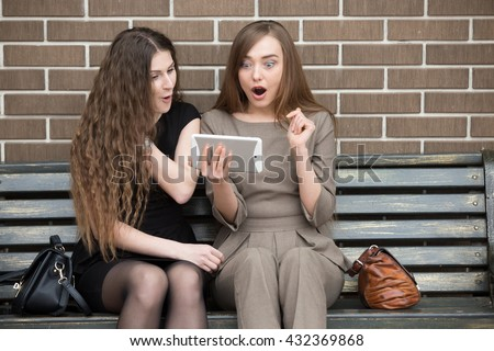 Portrait of two beautiful young surprised girlfriends sitting on bench and looking at tablet screen with shocked happy expressions. Attractive women friends found profitable deal or sale - stock photo