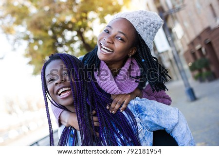 Portrait of two beautiful young woman looking at camera in the street.