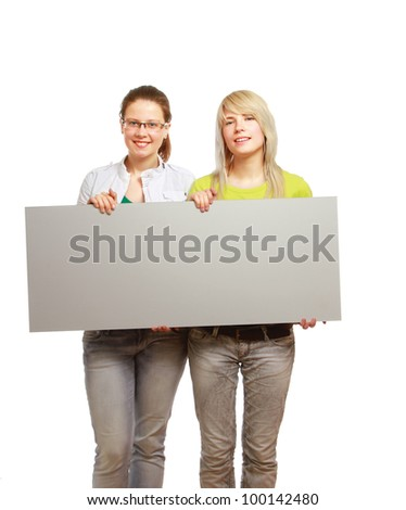 Portrait of two beautiful young women holding blank notecard isolated on white background - stock photo
