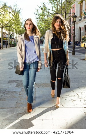 Portrait of two beautiful young women walking and talking in the street. - stock photo