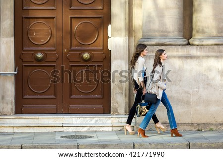 Portrait of two beautiful young women walking and talking in the street.