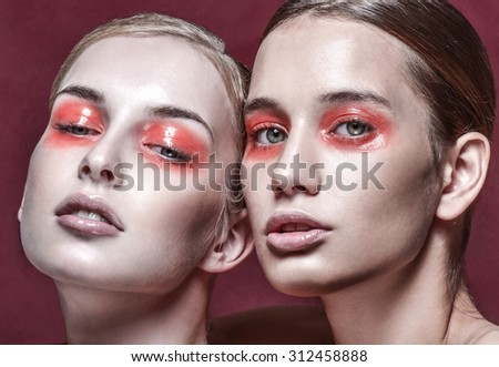 Portrait of two beautiful young women with bright fashion makeup. Professional makeup. - stock photo