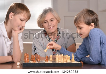 Portrait of two boys and grandmother playing chess at home - stock photo