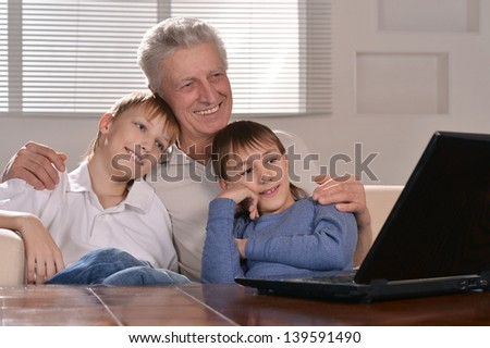Portrait of two boys and old men with laptop at home - stock photo