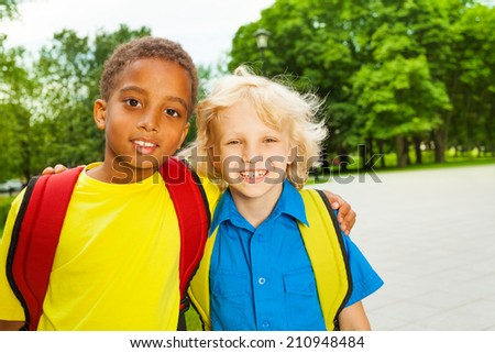 Portrait of two boys hugging on shoulders - stock photo