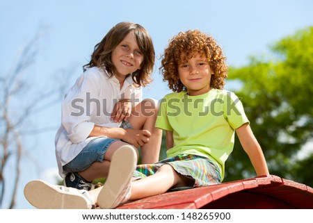 Portrait of two boys sitting together on rooftop in park.