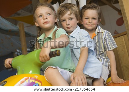 Portrait of two boys with a girl riding a tricycle - stock photo