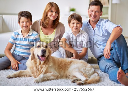 Portrait of two brothers, their parents and dog sitting on the floor