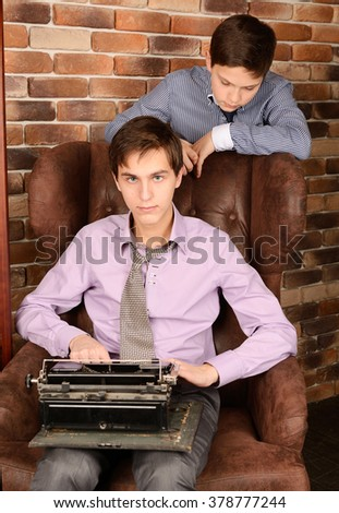 Portrait of two brothers with  old black typewriter