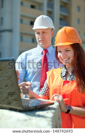 Portrait of two builders works at construction site