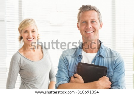 Portrait of two business colleagues holding a tablet at office - stock photo