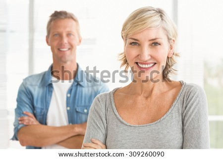 Portrait of two business colleagues with arms crossed at the office - stock photo