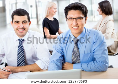 Portrait of two business men with colleagues behind them