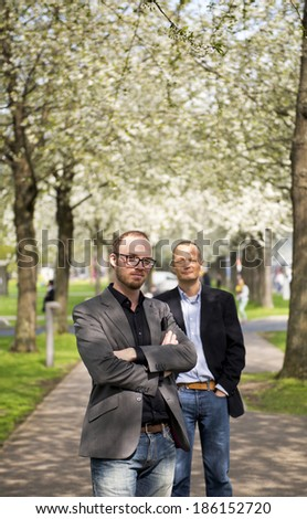 Portrait of two business partners, one standing in front of the other, posing on a footpath, underneath blossoming trees - stock photo