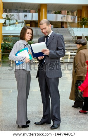 Portrait of two business people standing in the office looking into folder with business plan