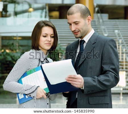 Portrait of two business people standing in the office looking into folder with business plan - stock photo