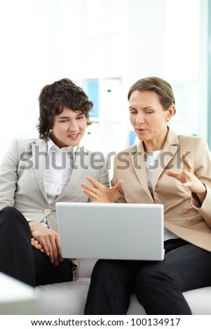 Portrait of two business women interacting in office