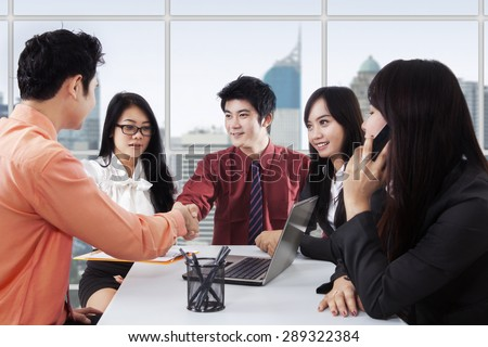 Portrait of two businessmen doing a meeting and a business agreement by shaking hands in the office - stock photo