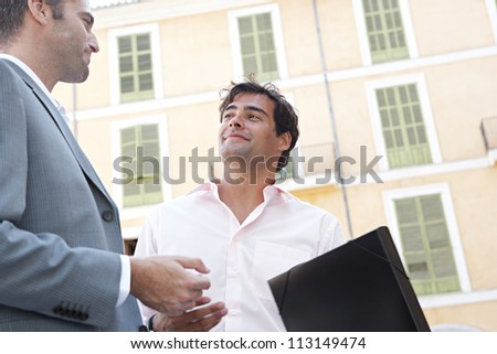 Portrait of two businessmen having a conversation while standing next to a classic building in the city. - stock photo