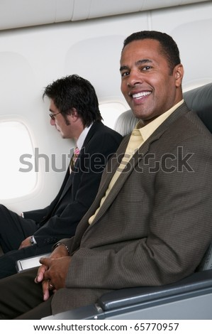 Portrait of two businessmen on airplane - stock photo