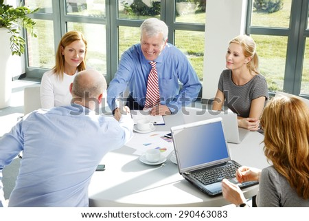Portrait of two businessmen shaking hands while making agreement and sitting at business meeting. Business people using laptop and digital tablet while sitting around conference table.