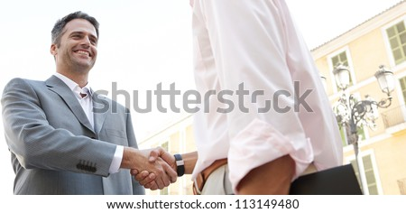 Portrait of two businessmen shaking hands while standing in front of a classic European building, outdoors. - stock photo