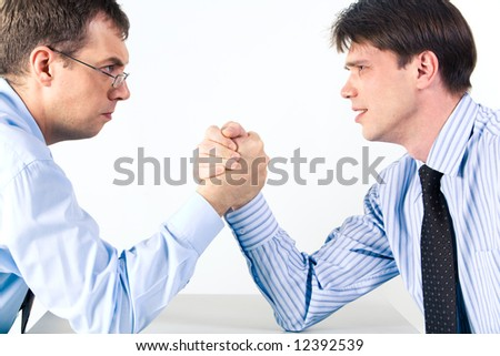 Portrait of two businessmen sitting opposite each other elbowing on the table with their arms grappled in fight - stock photo