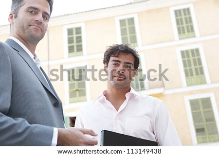 Portrait of two businessmen standing next to a classic building in the city, smiling. - stock photo